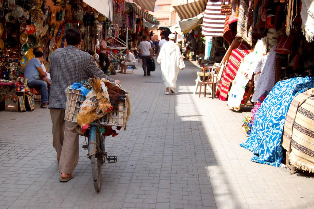 Homme poussant un vélo dans le souk de Marrakech